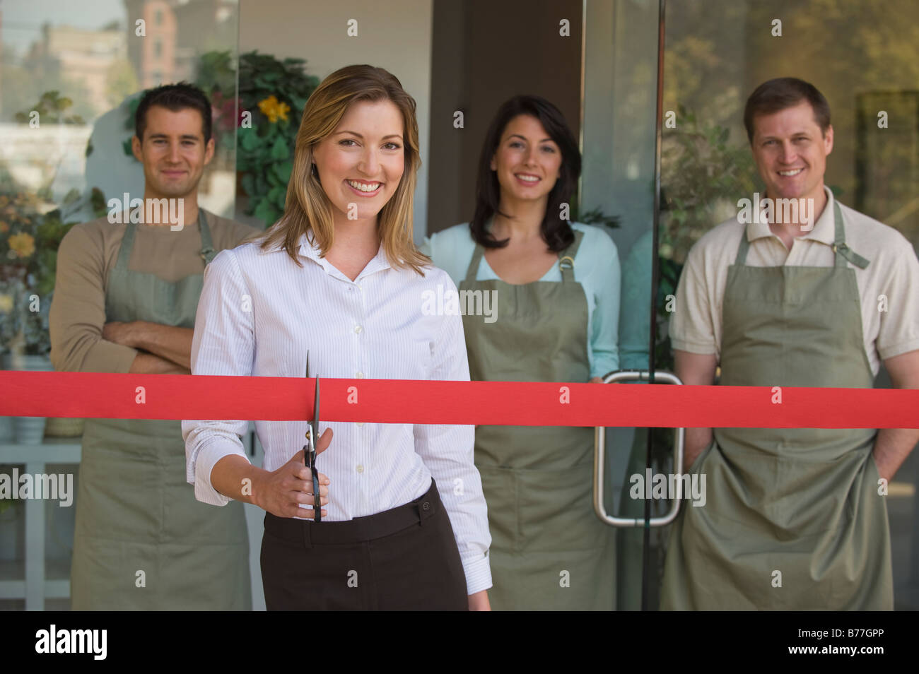 small business owner cutting red ribbon grand opening stock photo