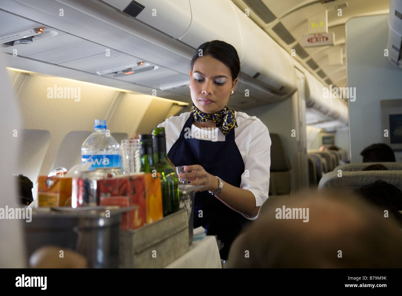 Cabin crew / air stewardess serves drinks to passengers from a trolley cart during a flight (45) Stock Photo