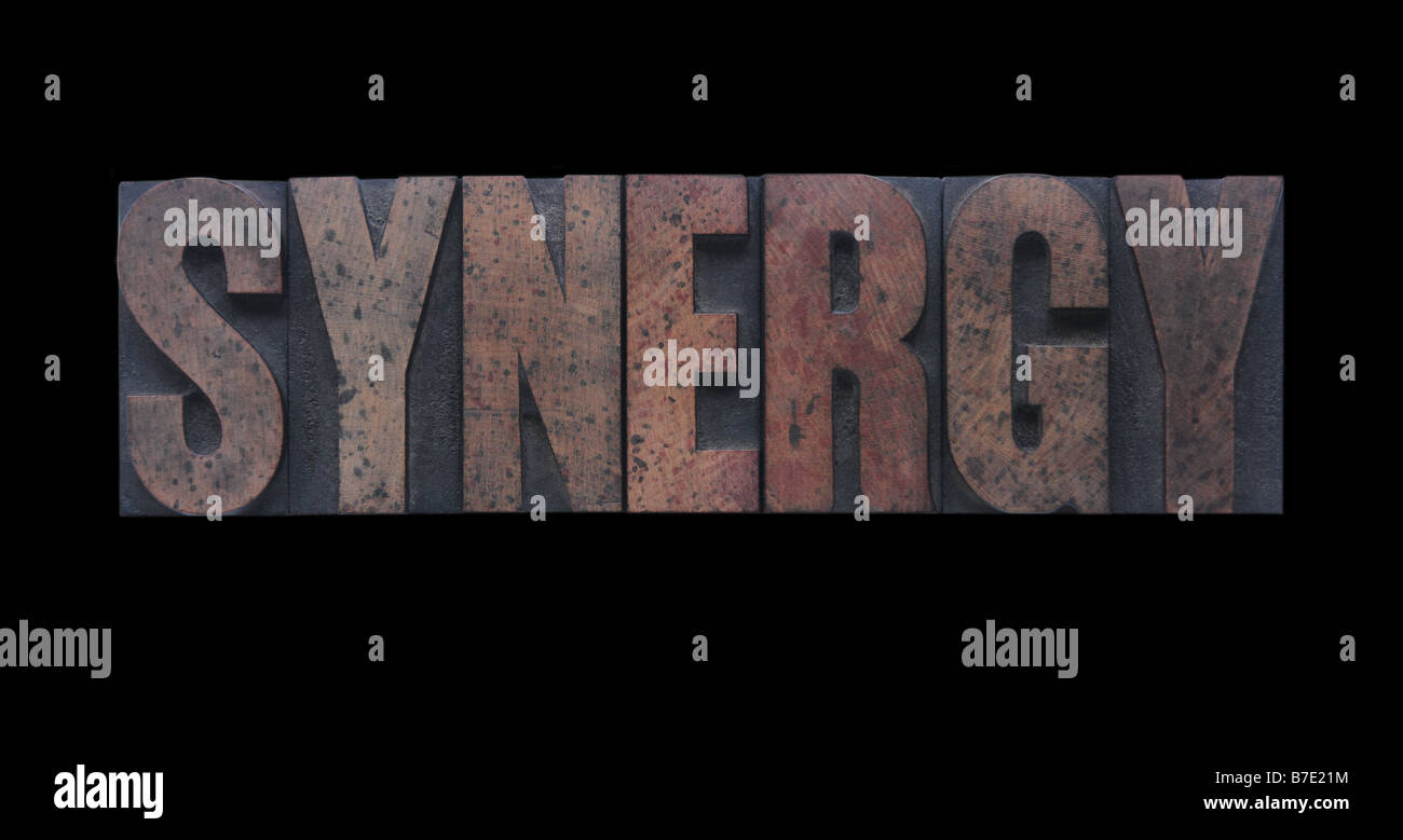 the word 'synergy' in old ink-stained wood type - Stock Image
