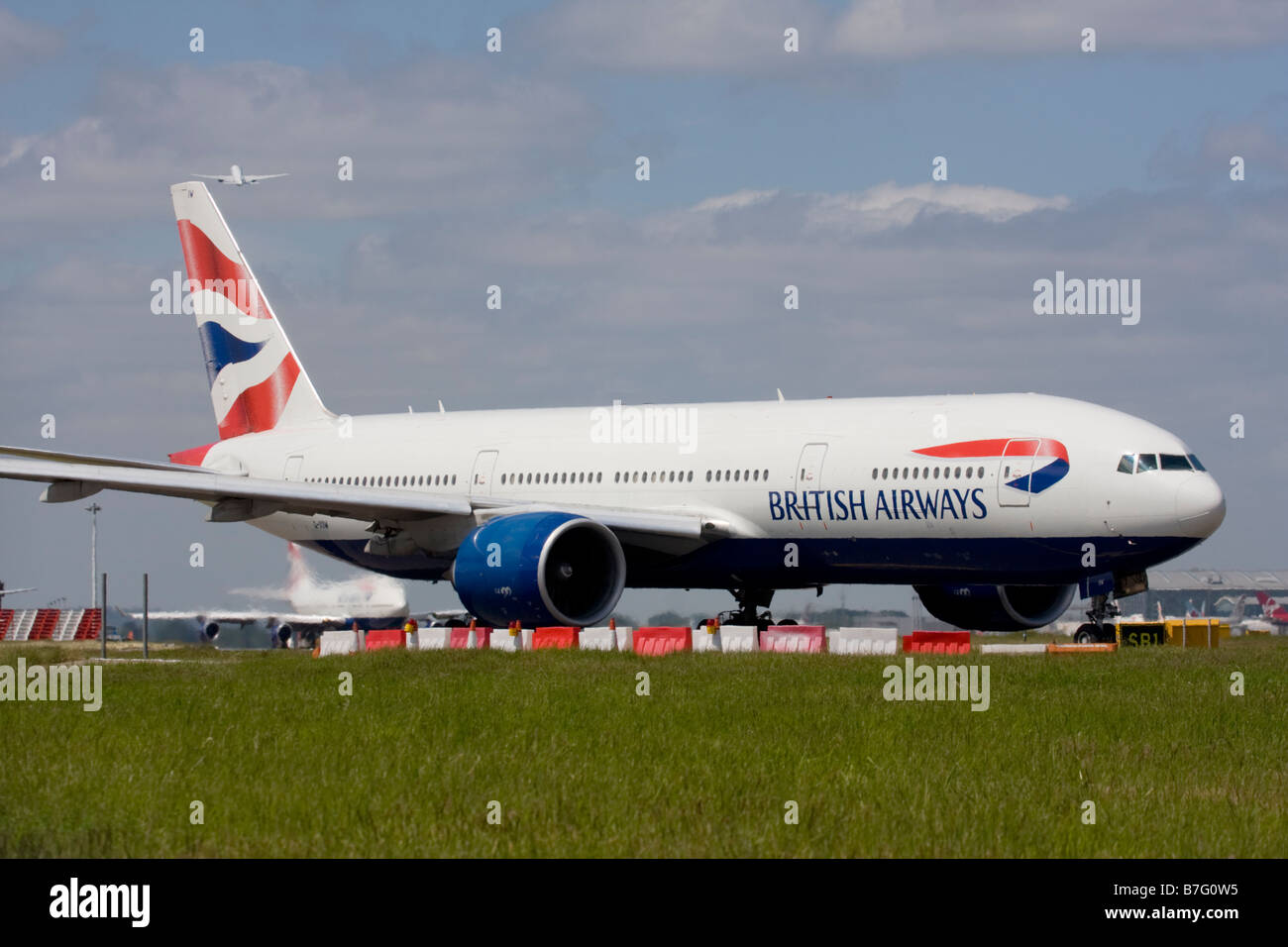 British Airways Boeing 777-236/ER and another commercial airplane taking off in the background at London Heathrow Stock Photo