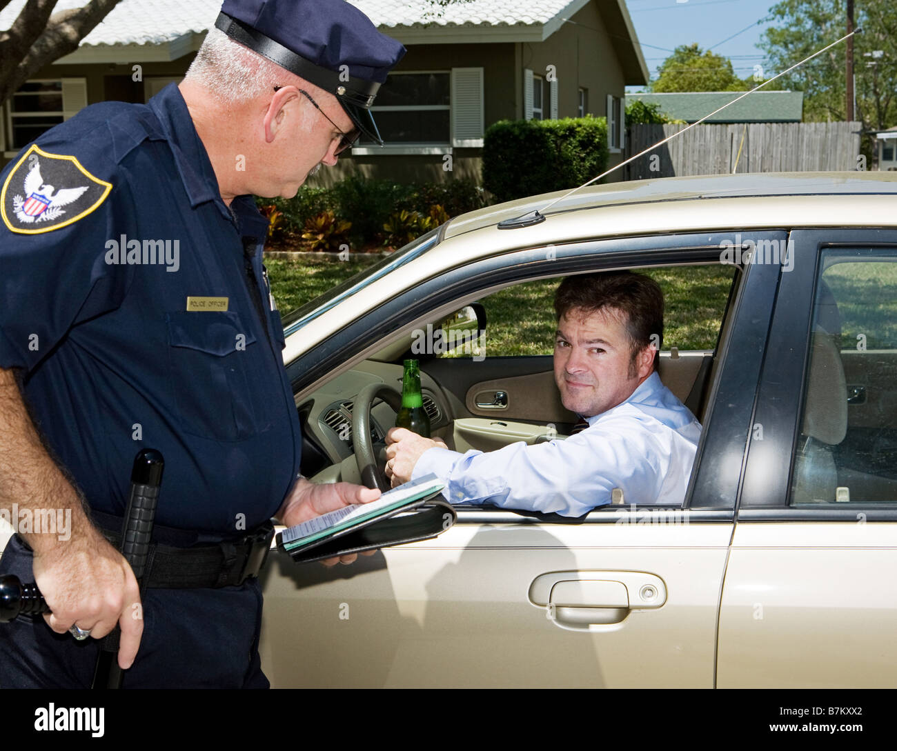 Police officer pulling over a drunk driver The driver is holding a beer and looking embarassed - Stock Image