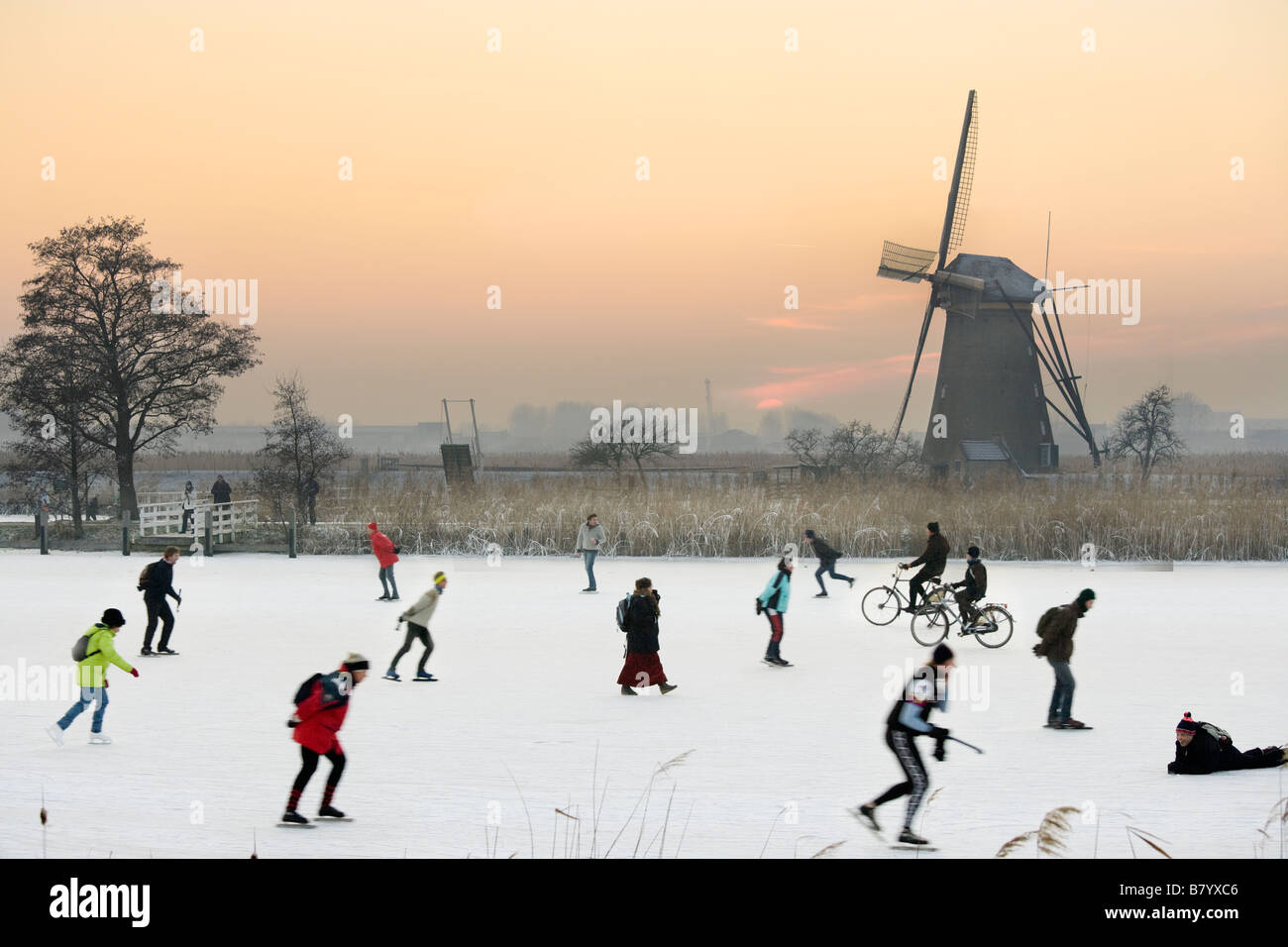 Ice skaters and even cyclists on natural ice in front of a windmill at Kinderdijk Holland, The Netherlands. At sunset. Stock Photo