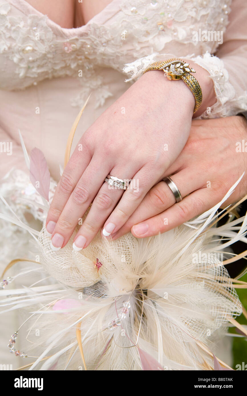 bride and grooms wedding ring on hands over vintage themed bouquet ...