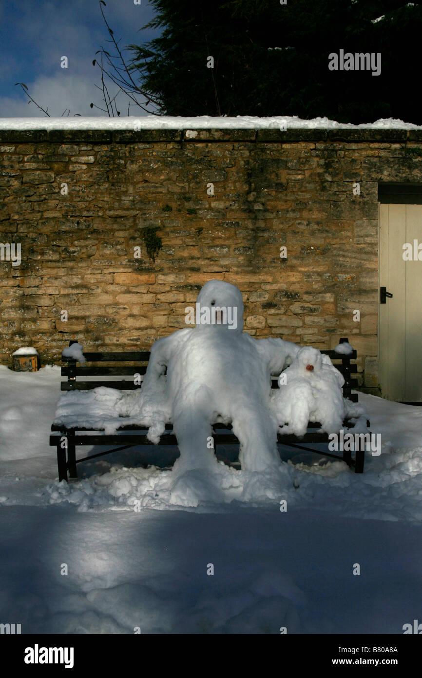 Snowmen on bench, Great Barrington, Oxfordshire, Cotswolds UK - Stock Image