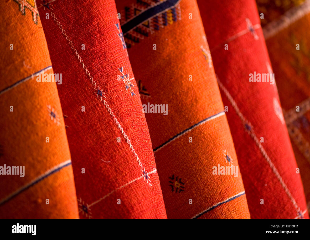 Red and orange Morrocan rugs hung for sale in the souks of Marrakech, Morocco - Stock Image