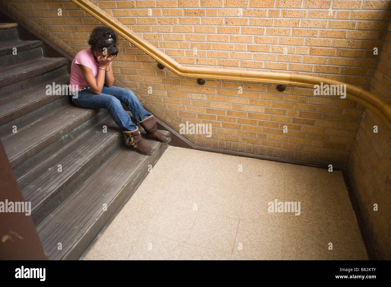 teenage african american girl crying on staircase at school, sitting on step - Stock Image