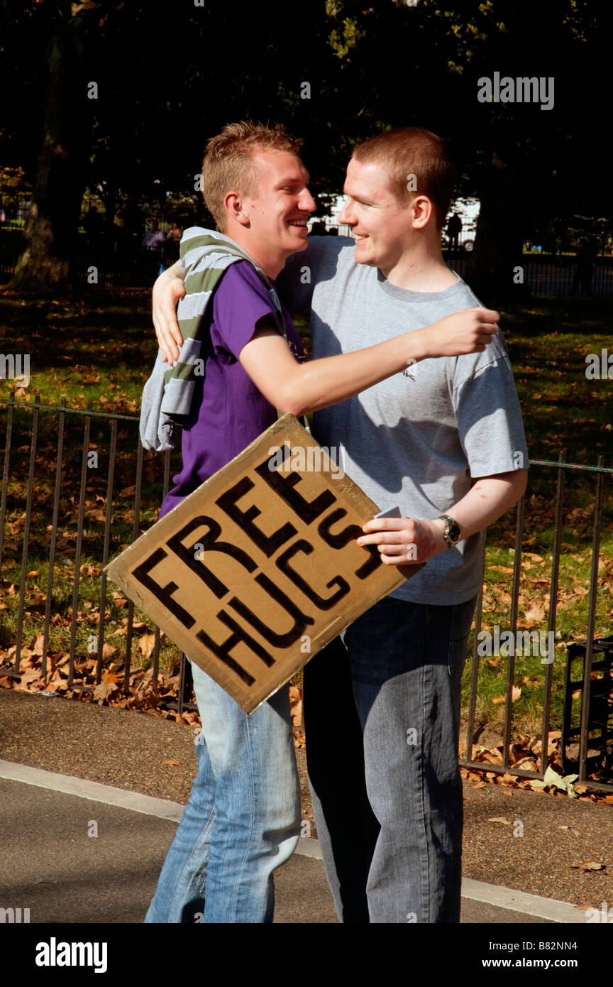 A man carrying a Free Hugs sign hugging a a man at speakers corner Stock Photo