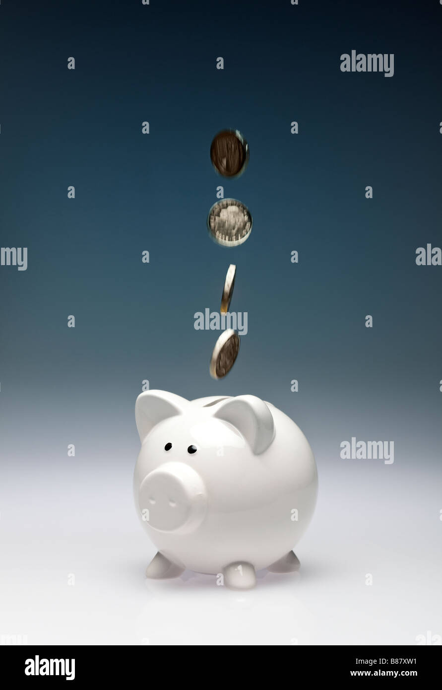 Concept finance saving - Pound coins sterling falling into a piggy bank - studio - Stock Image