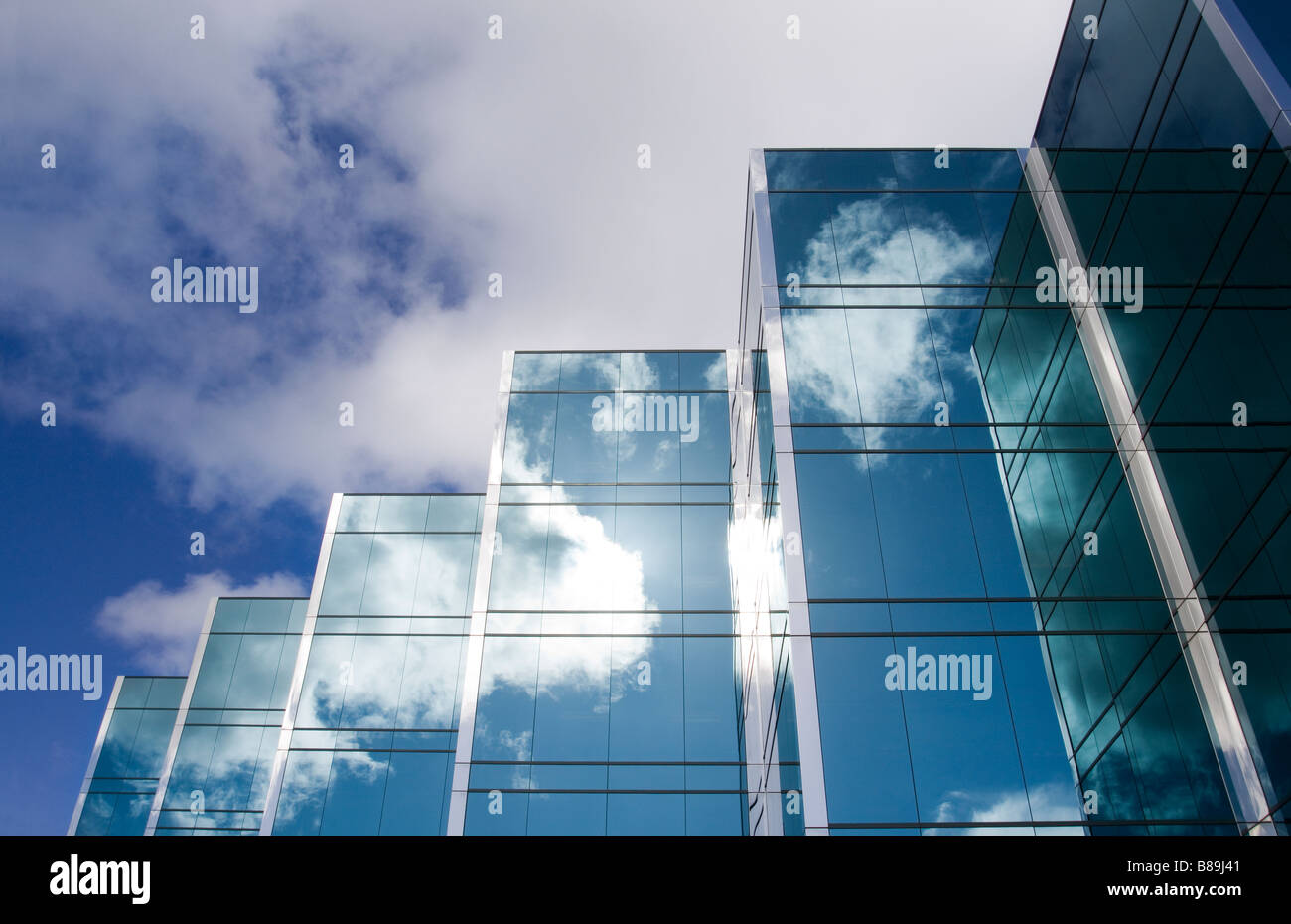 Five towers of a sleek modern glass office building with clouds and sky reflecting on the surface of the buildings - Stock Image
