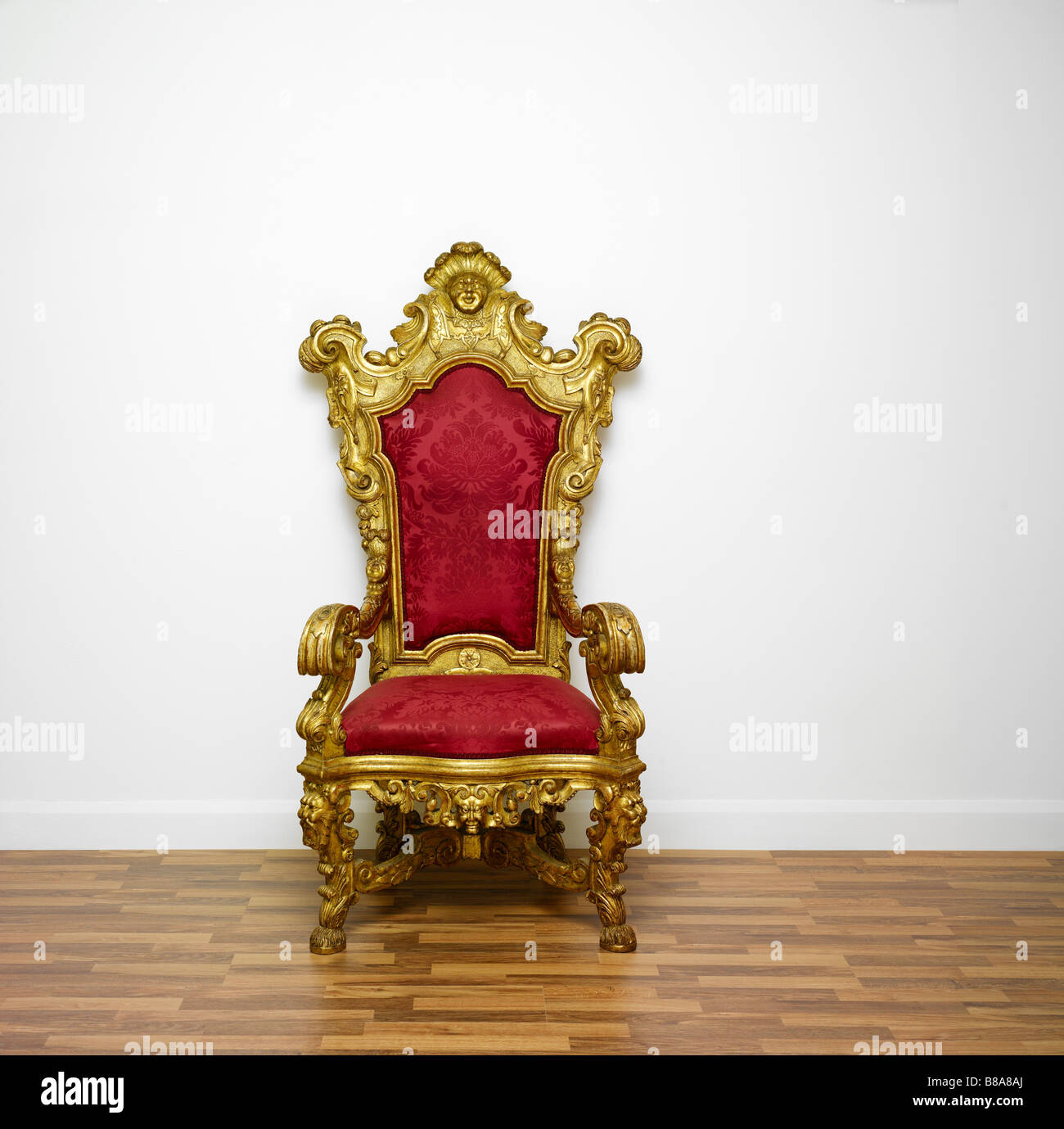 A red and gold throne chair on a white background - Stock Image
