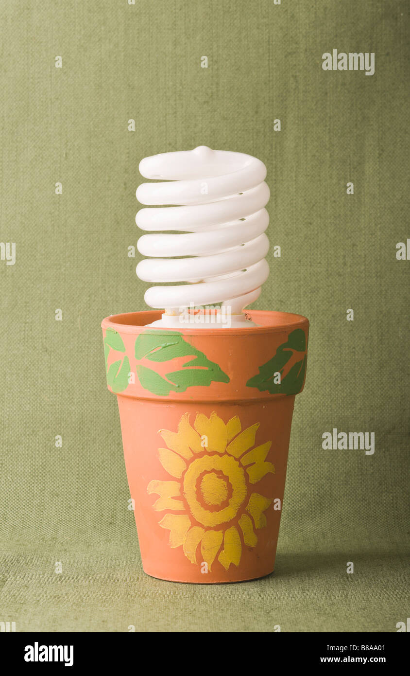 Ecofriendly solution concept symbol metaphor energy saving compact fluorescent bulb panted in clay pot isolated Stock Photo