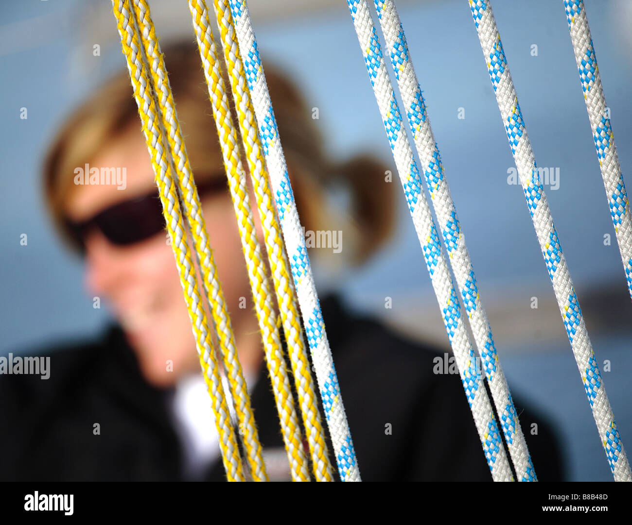 girl, European white female sailor  out of focus against rigging of a yacht. - Stock Image