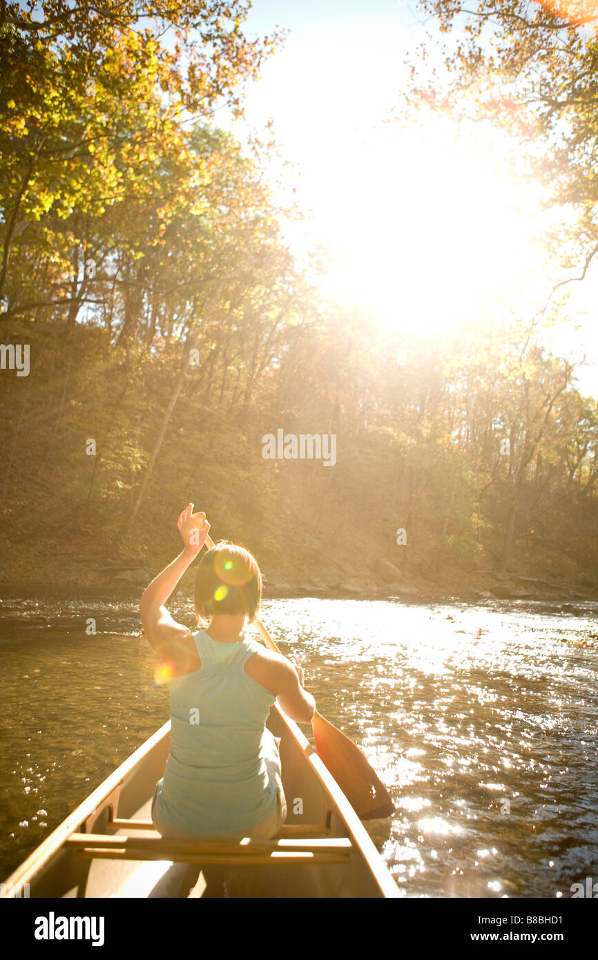 Woman canoeing down the river - Stock Image