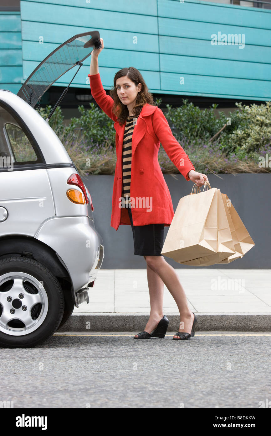 Woman by car with shopping bags - Stock Image