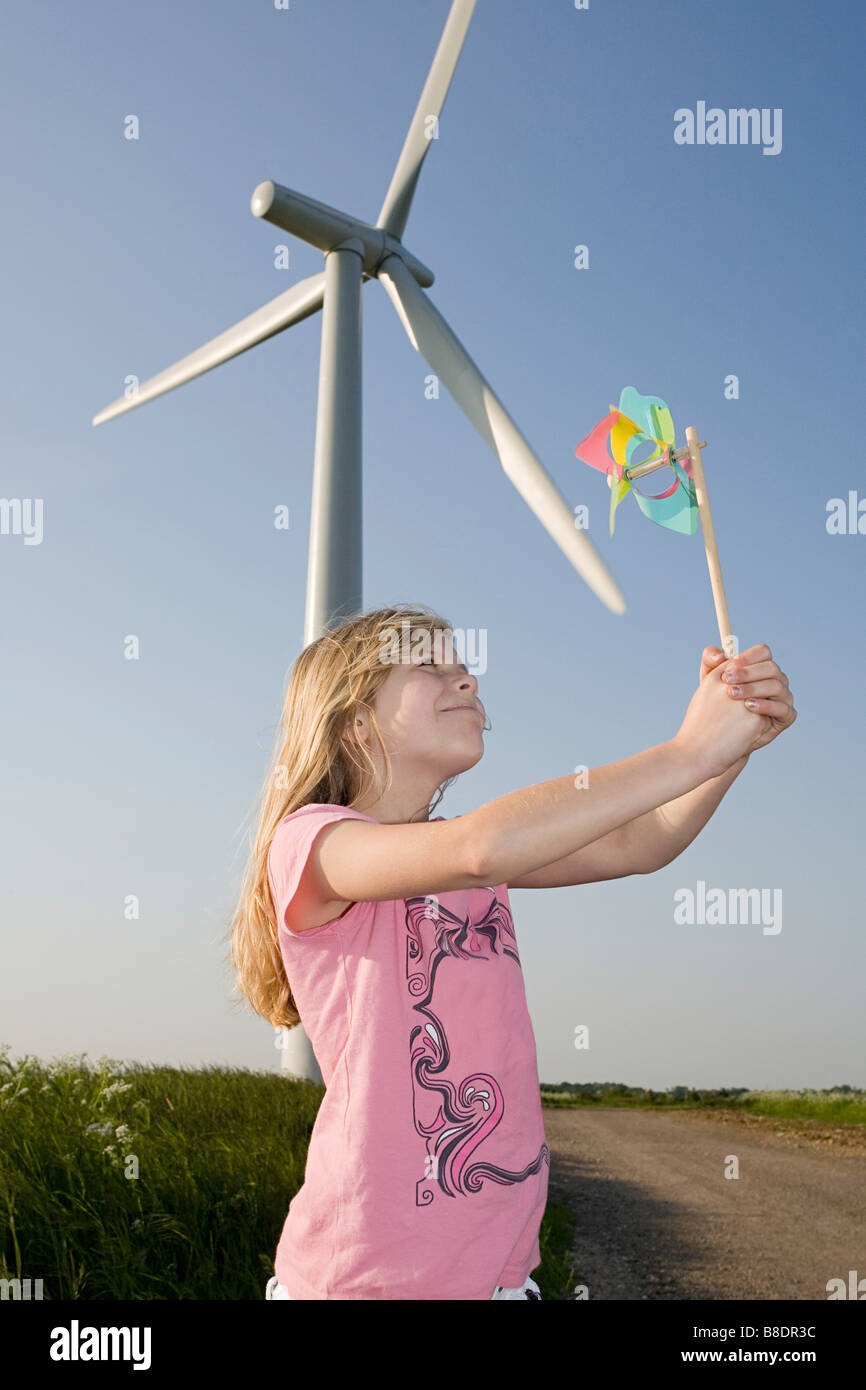 Girl with pinwheel by wind turbine - Stock Image