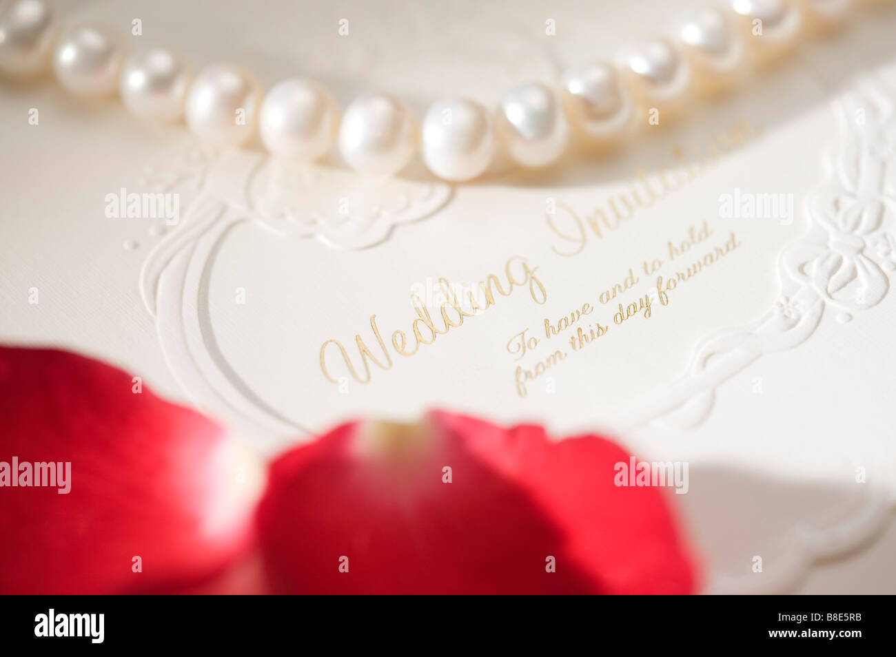 Pearl necklace and rose petals on wedding invitation Stock Photo ...