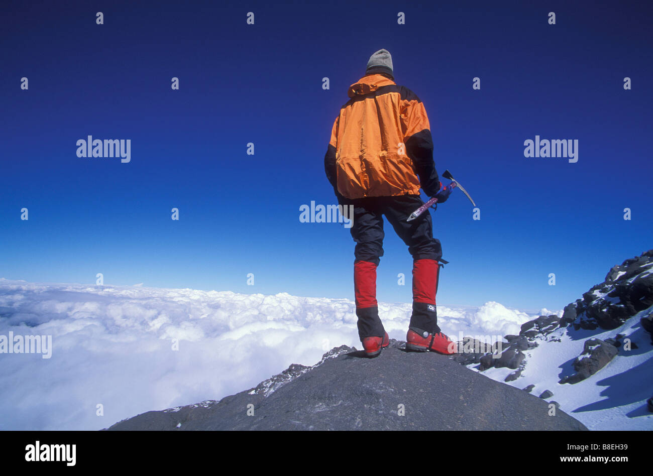 Mountain climber enjoys the view in distance while standing on El Pico de Orizaba in Mexico - Stock Image