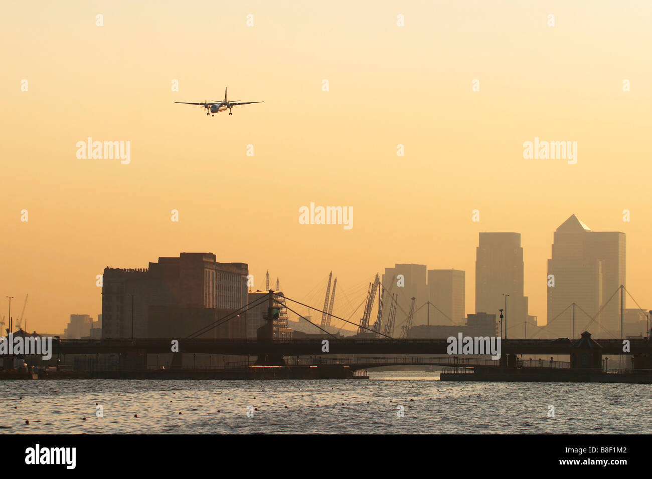 Regional airliner landing at London City Airport with Canary Wharf Docklands in the background, UK - Stock Image