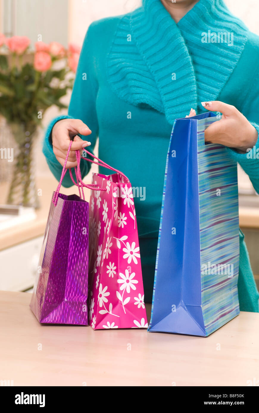 Woman arriving home with shopping bags - Stock Image