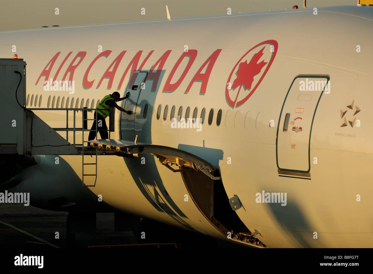 An airport technician closing the door on an Air Canada plane Stock Photo