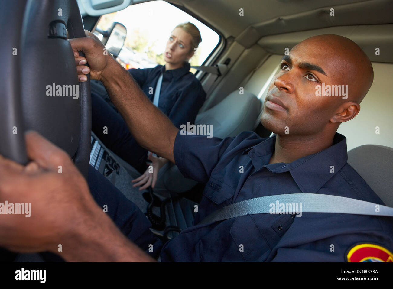 Ambulance driver and colleague on the way to an emergency - Stock Image