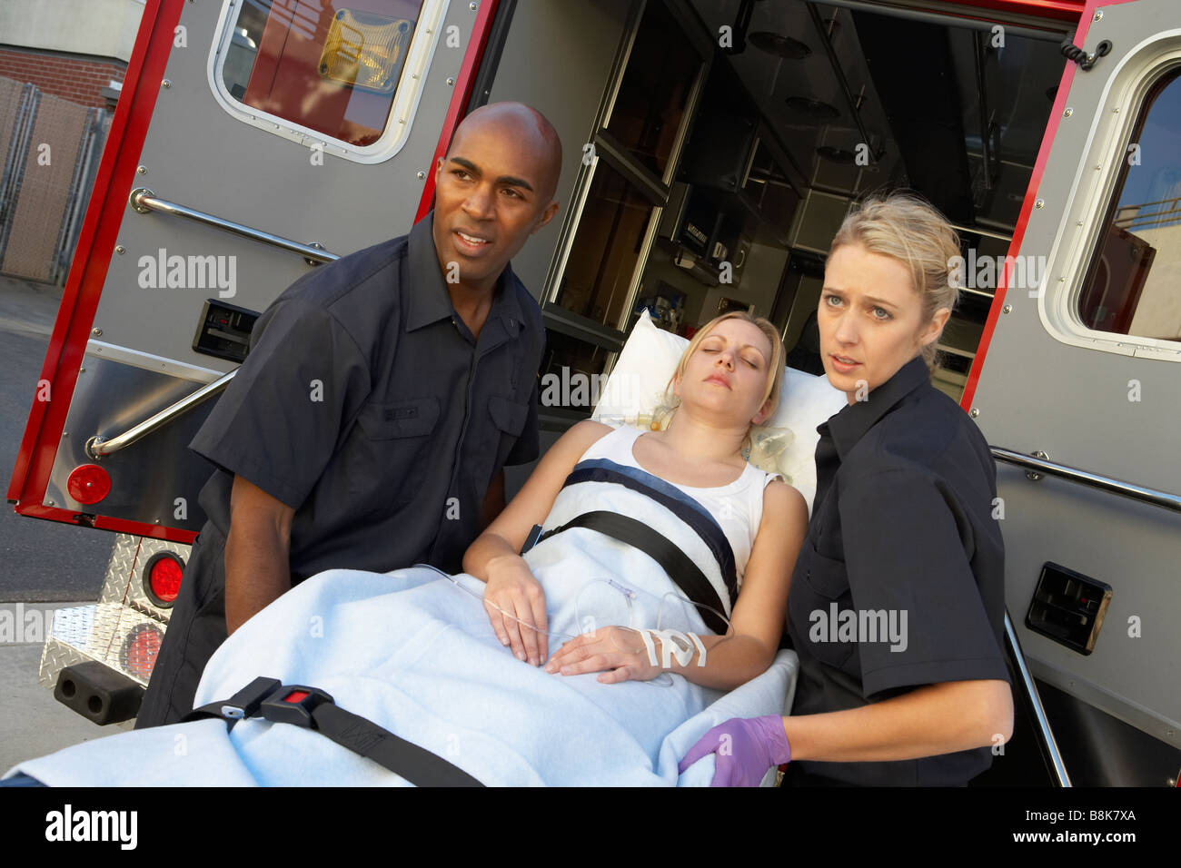 Paramedics unloading patient from ambulance - Stock Image