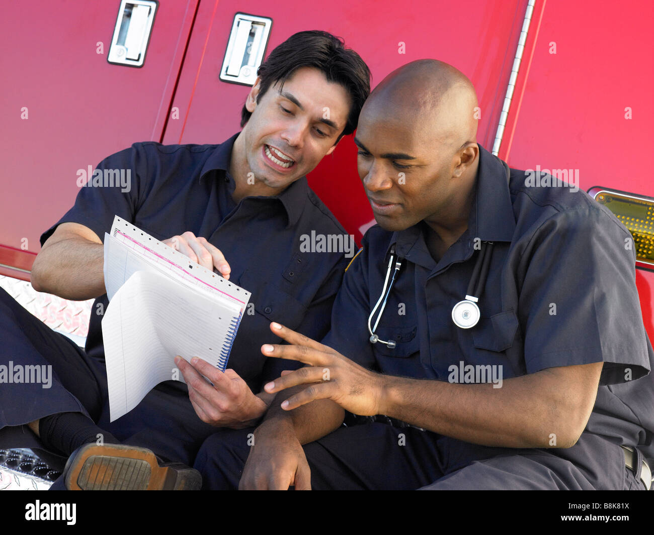Two paramedics cheerfully doing paperwork, sitting by their ambulance - Stock Image