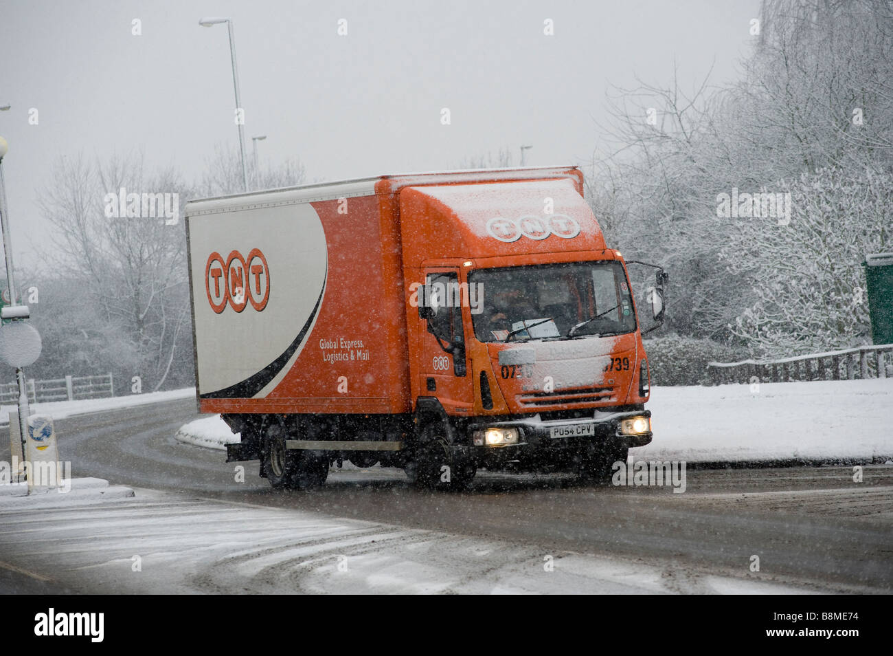 Driving a TNT delivery lorry through snow and ice to make deliveries on a winters day in England - Stock Image