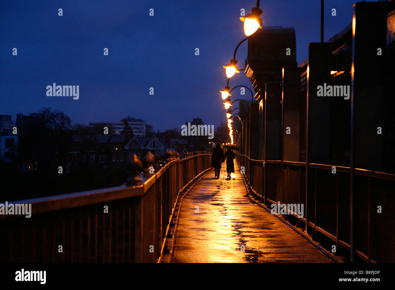 Pedestrians walking across a wet Fulham Rail Bridge, Fulham, London - Stock Image