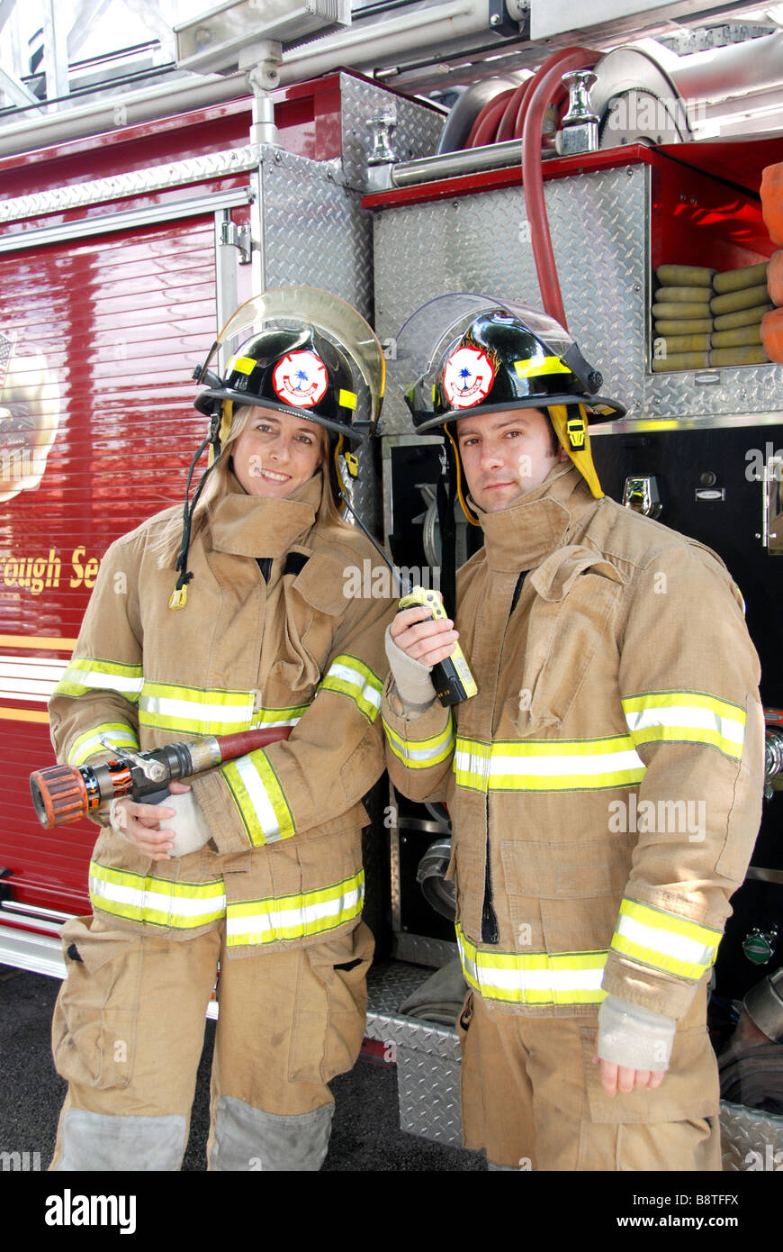 Male and Female Firefighters standing in front of fire truck with radio and hose - Stock Image