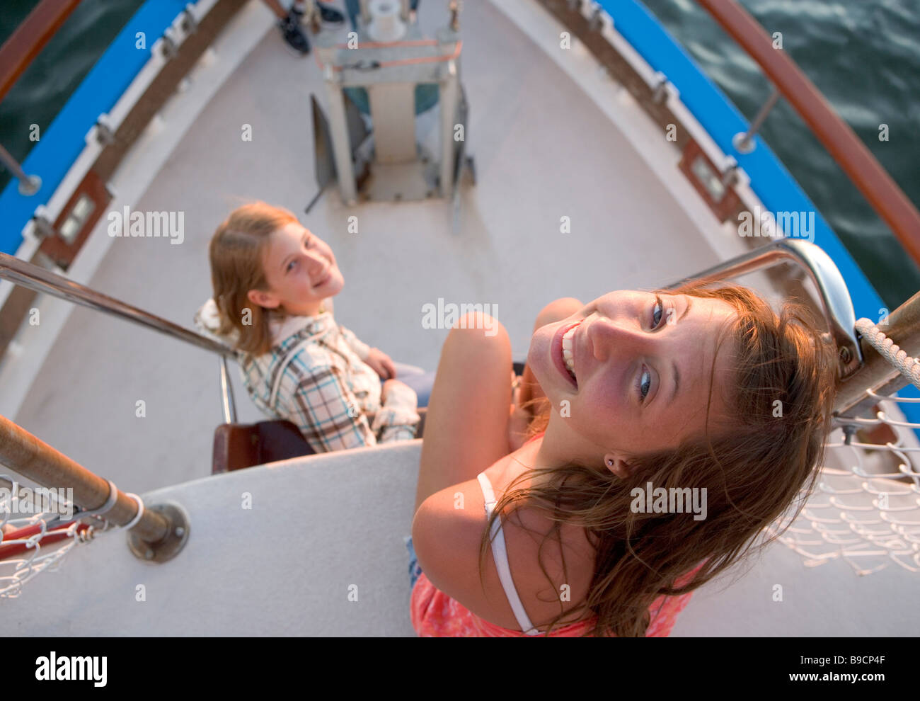 Two teen-aged girls near the bow of a tour boat at sunset - Stock Image