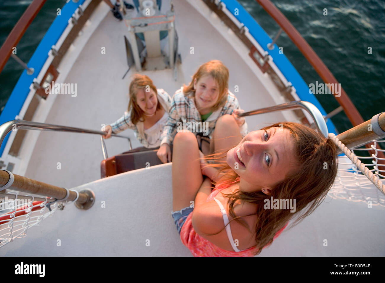 Three teen-aged girls near the bow of a tour boat at sunset - Stock Image