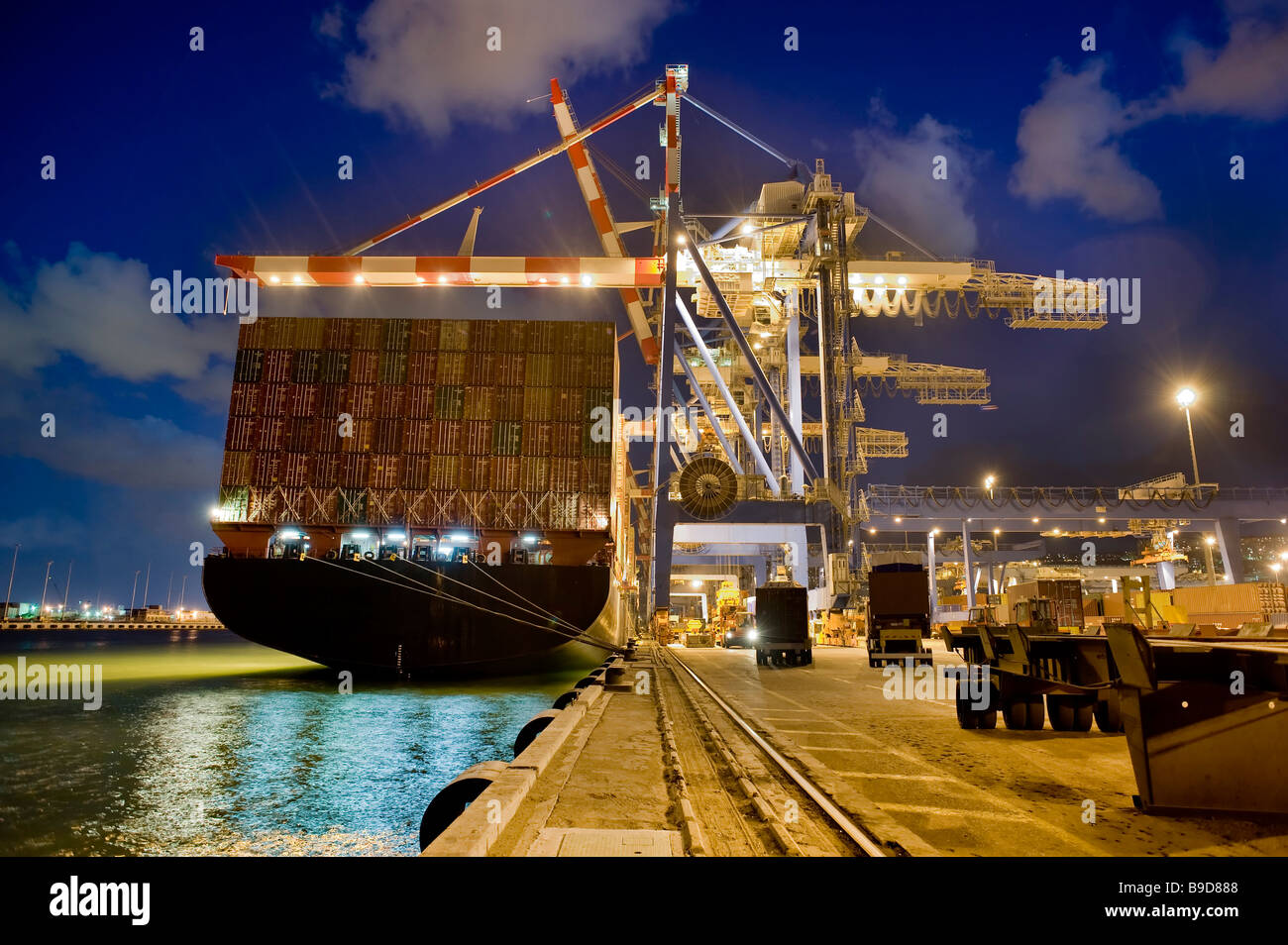 cargo ship at dock by night from behind - Stock Image