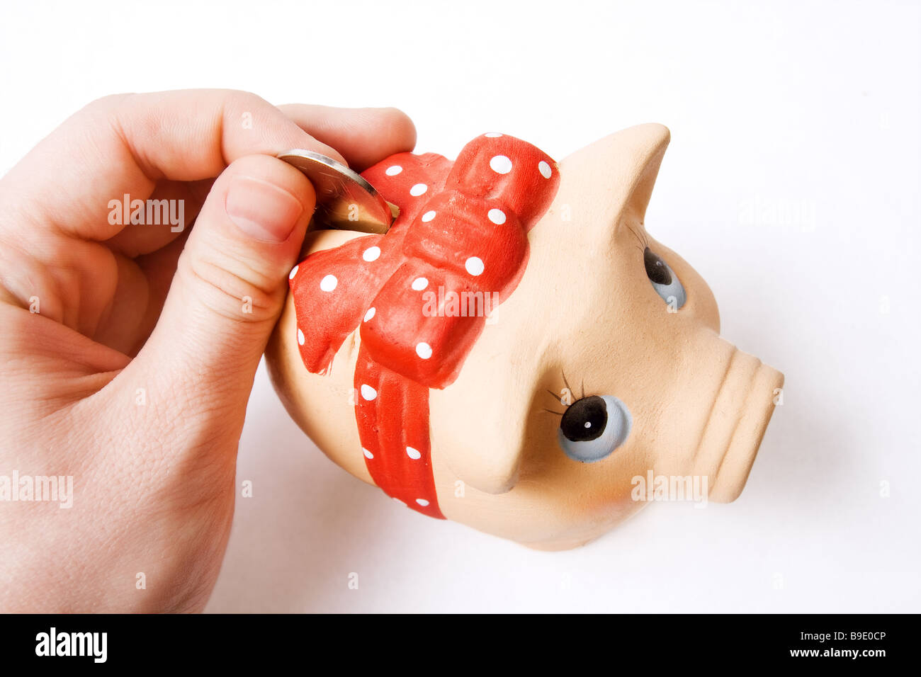 Saving money concept coin inserted in cute piggy bank - Stock Image