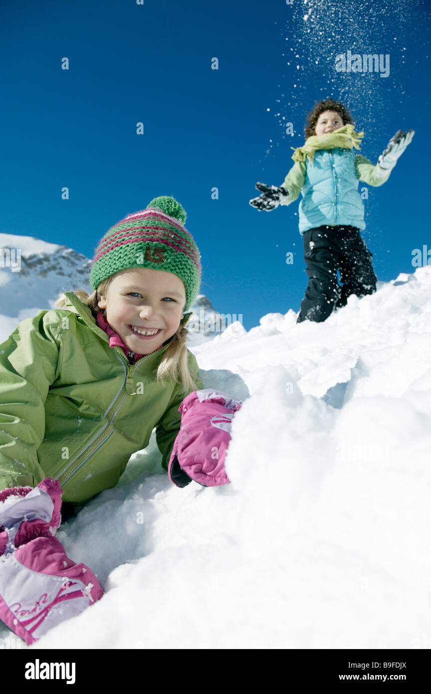 Portrait of girl smiling on snowcovered landscape with boy in background - Stock Image