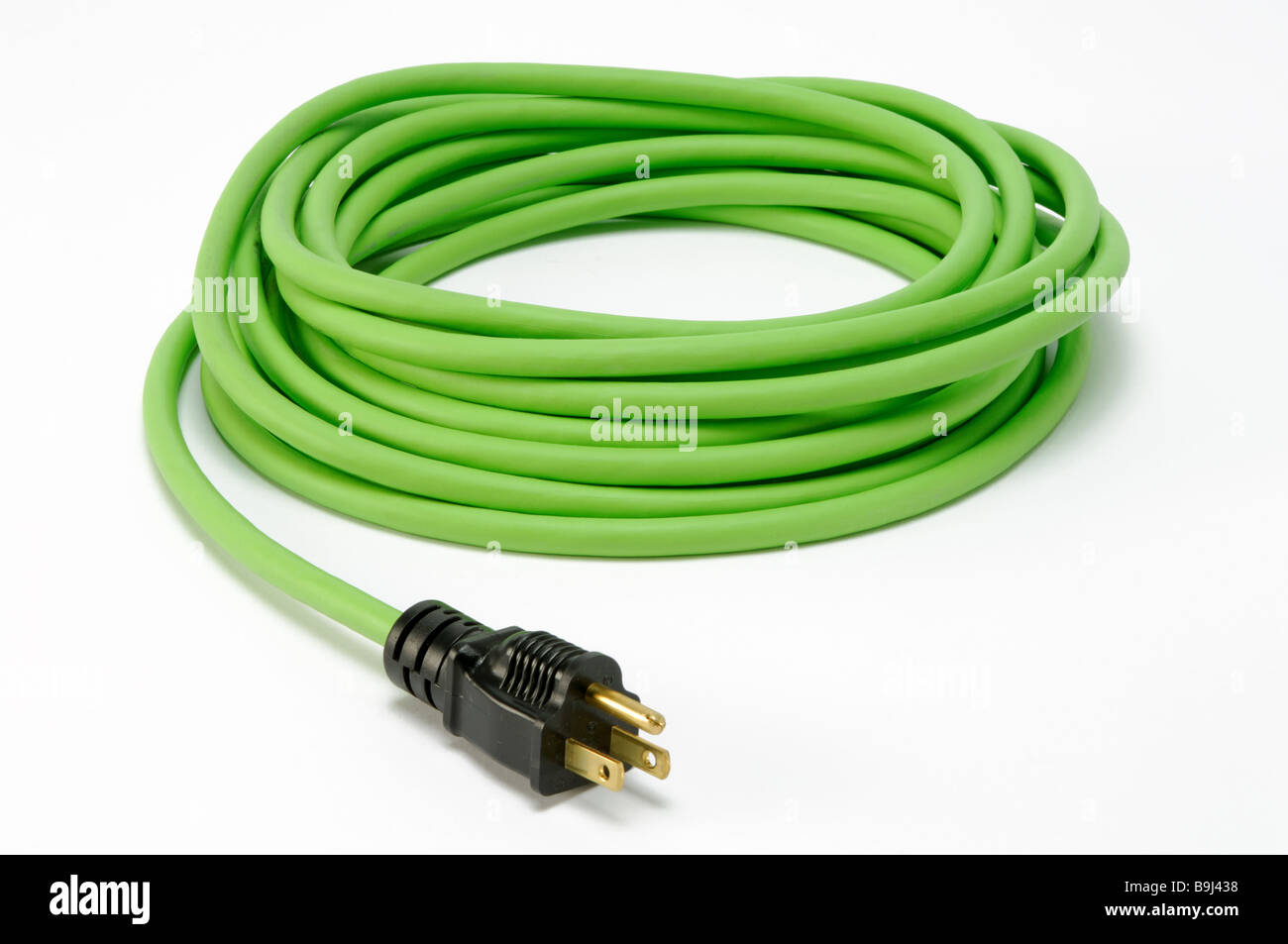 A coiled green electrical extension power cord with one plug - Stock Image