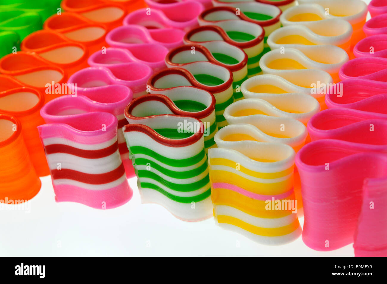 Close up of diagonal strips of colorful twisted thin ribbon candy - Stock Image