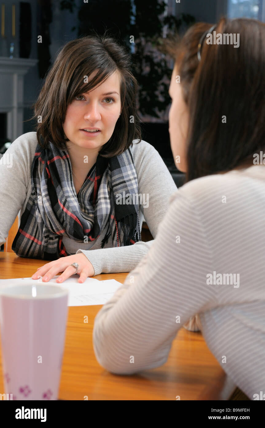 Young female tutor home teaching a teenage girl at the dining room table - Stock Image