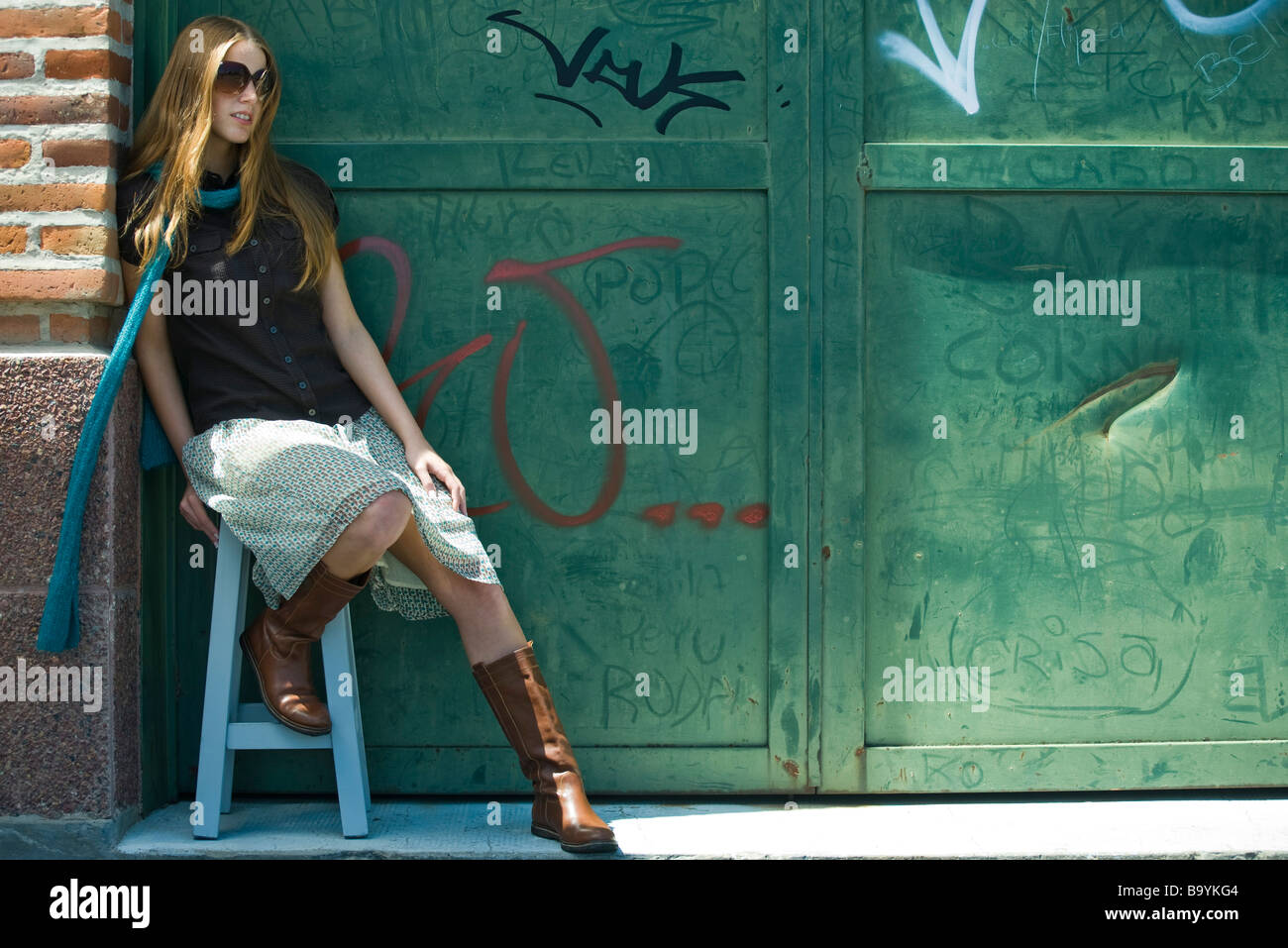 Trendy young woman sitting on stool in front of graffitied wall - Stock Image