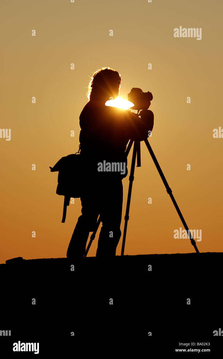 A photographer silhouetted against the setting sun Stock Photo
