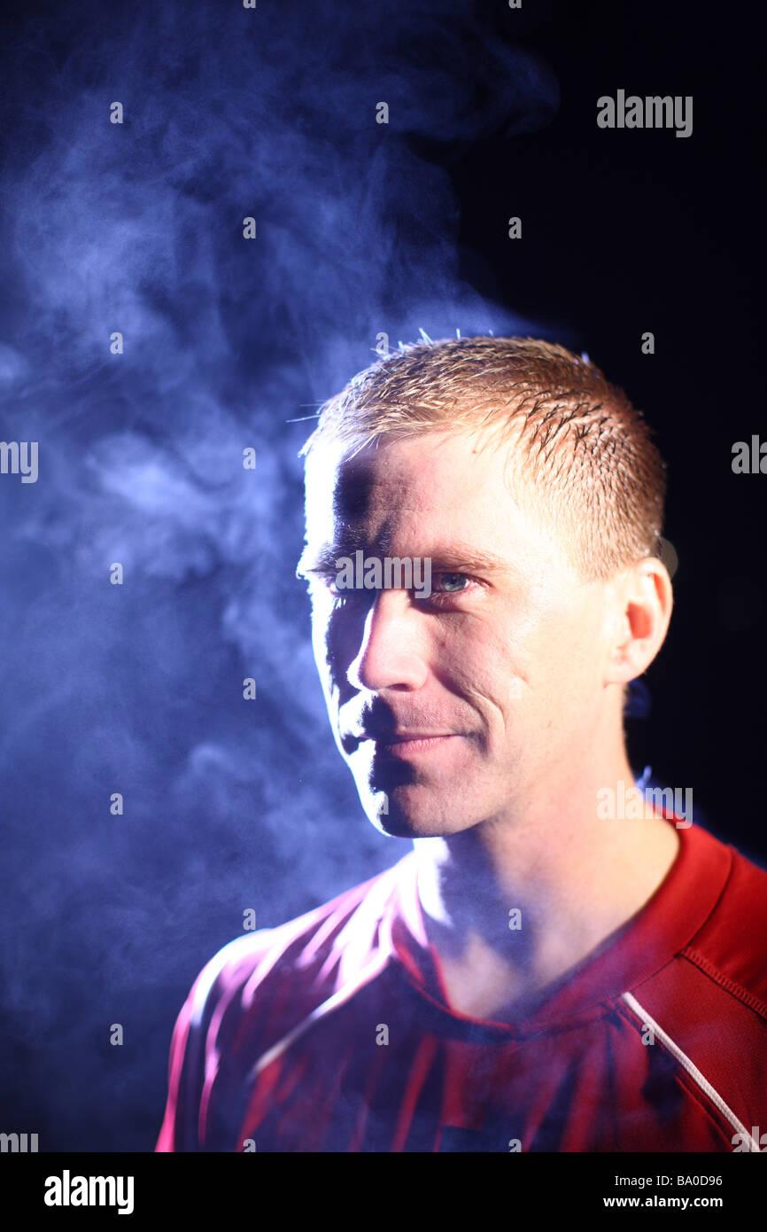 Athlete on cold dark night with steam - Stock Image