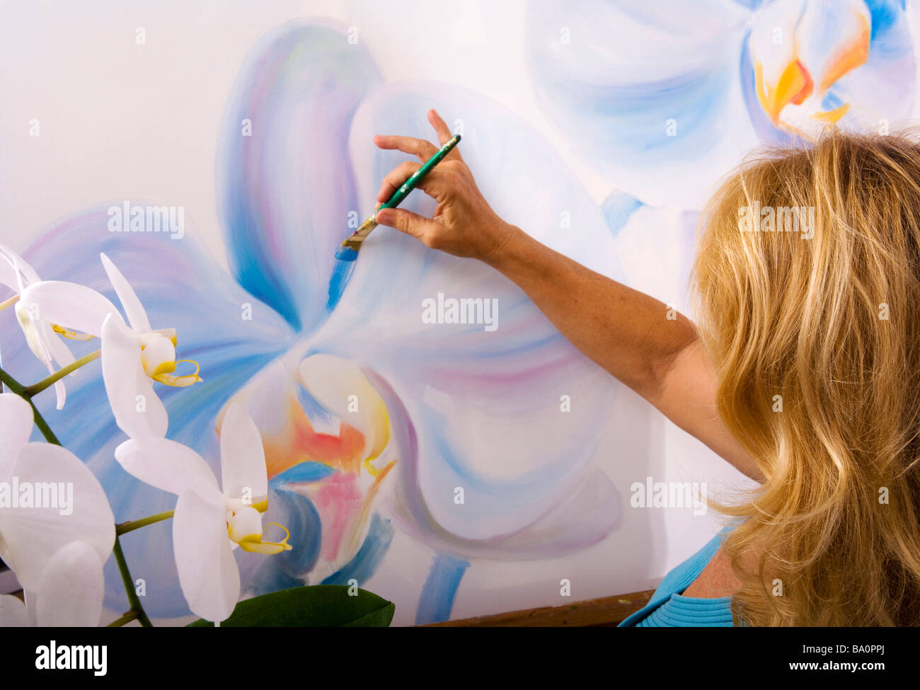 A female artist painting phalaenopsis orchids on canvas in her studio - Stock Image
