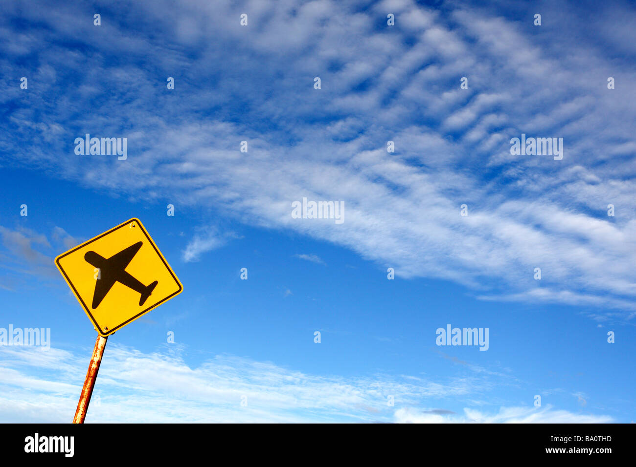 Airplane sign against blue sky - Stock Image