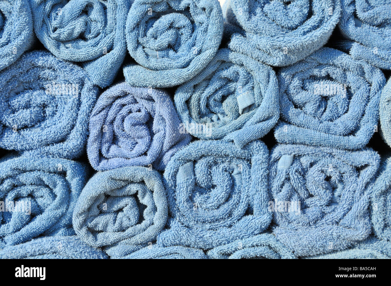 Background abstract  close up end view of blue rolled up towels in stacks beside pool awaiting use by cruise ship - Stock Image