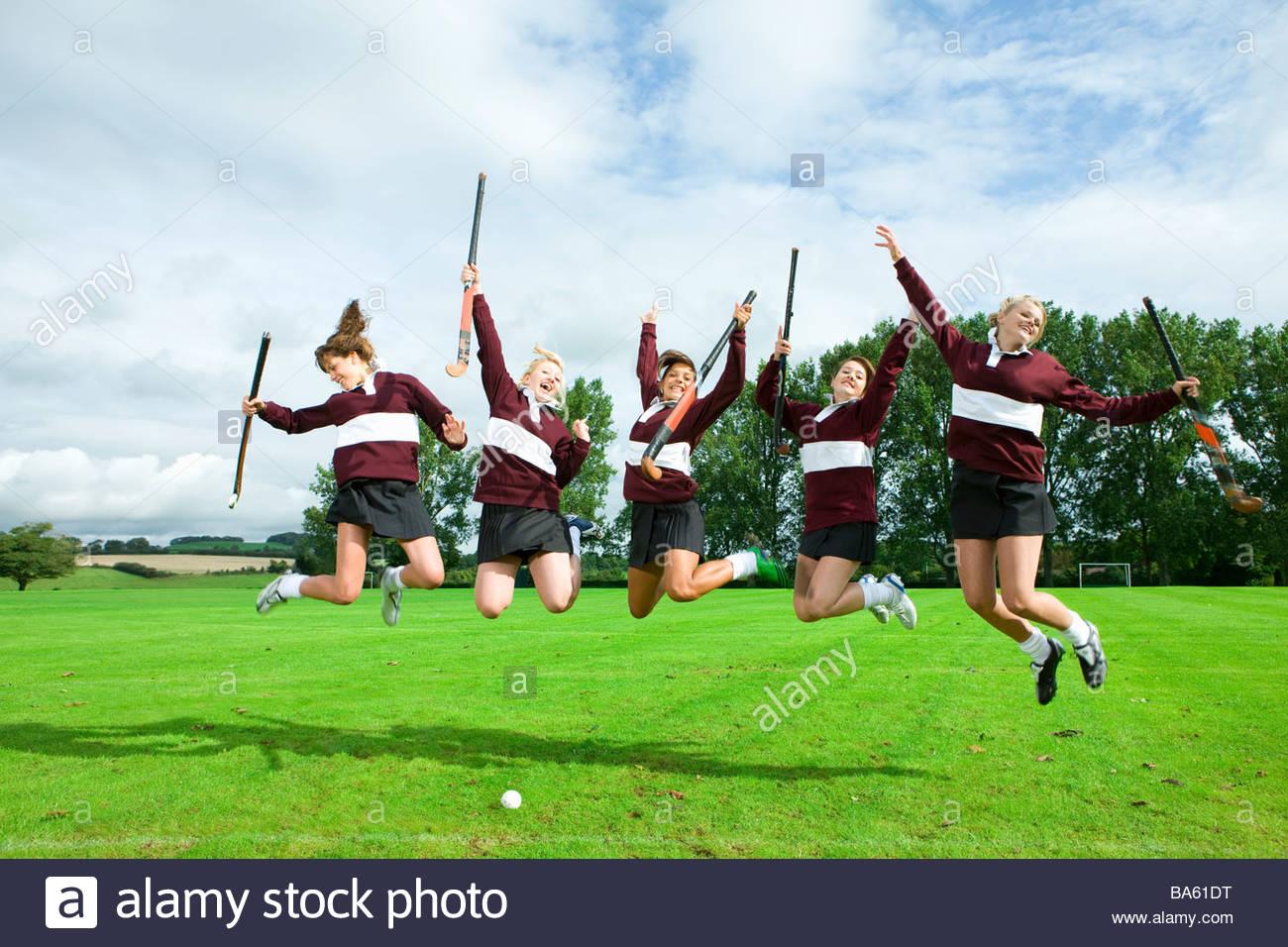Teenage girl hockey team jumping on field - Stock Image