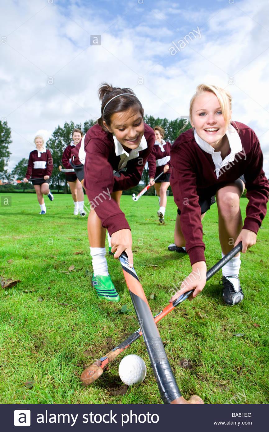 Portrait of smiling teenage girls playing field hockey - Stock Image