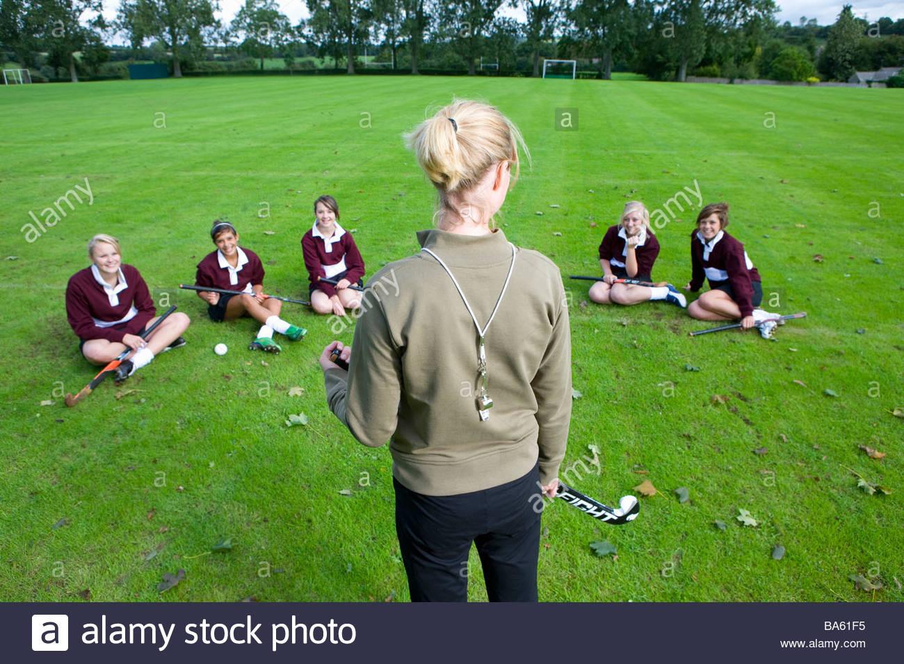 Coach standing before teenage girl field hockey team - Stock Image