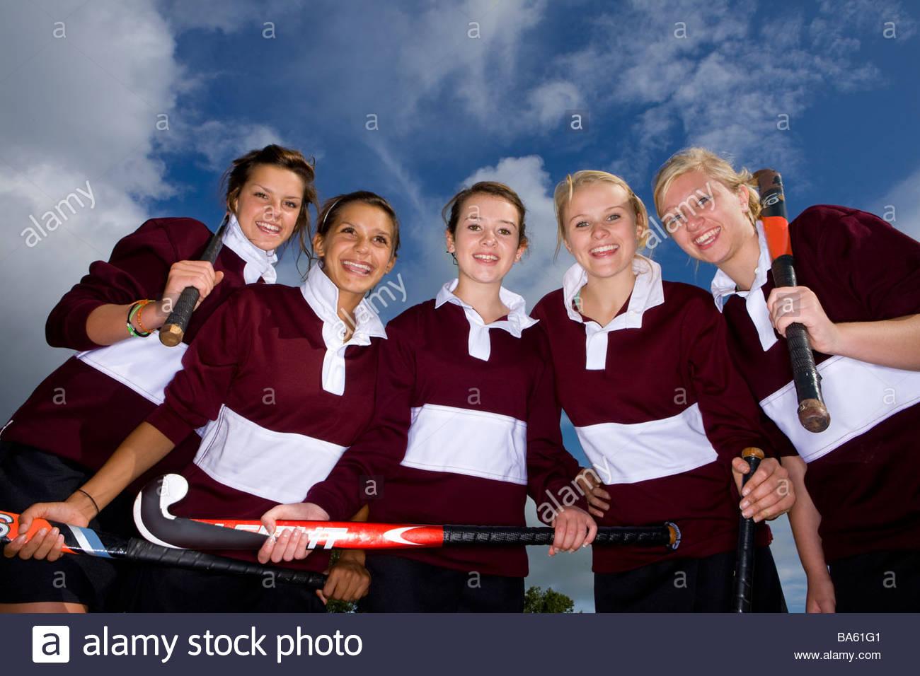 Portrait of smiling teenage girls holding field hockey sticks - Stock Image