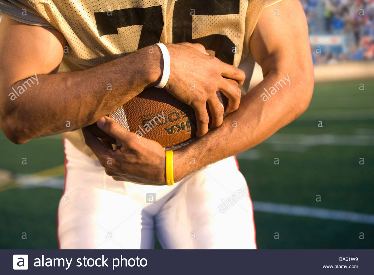 Close up of football player holding football - Stock Image