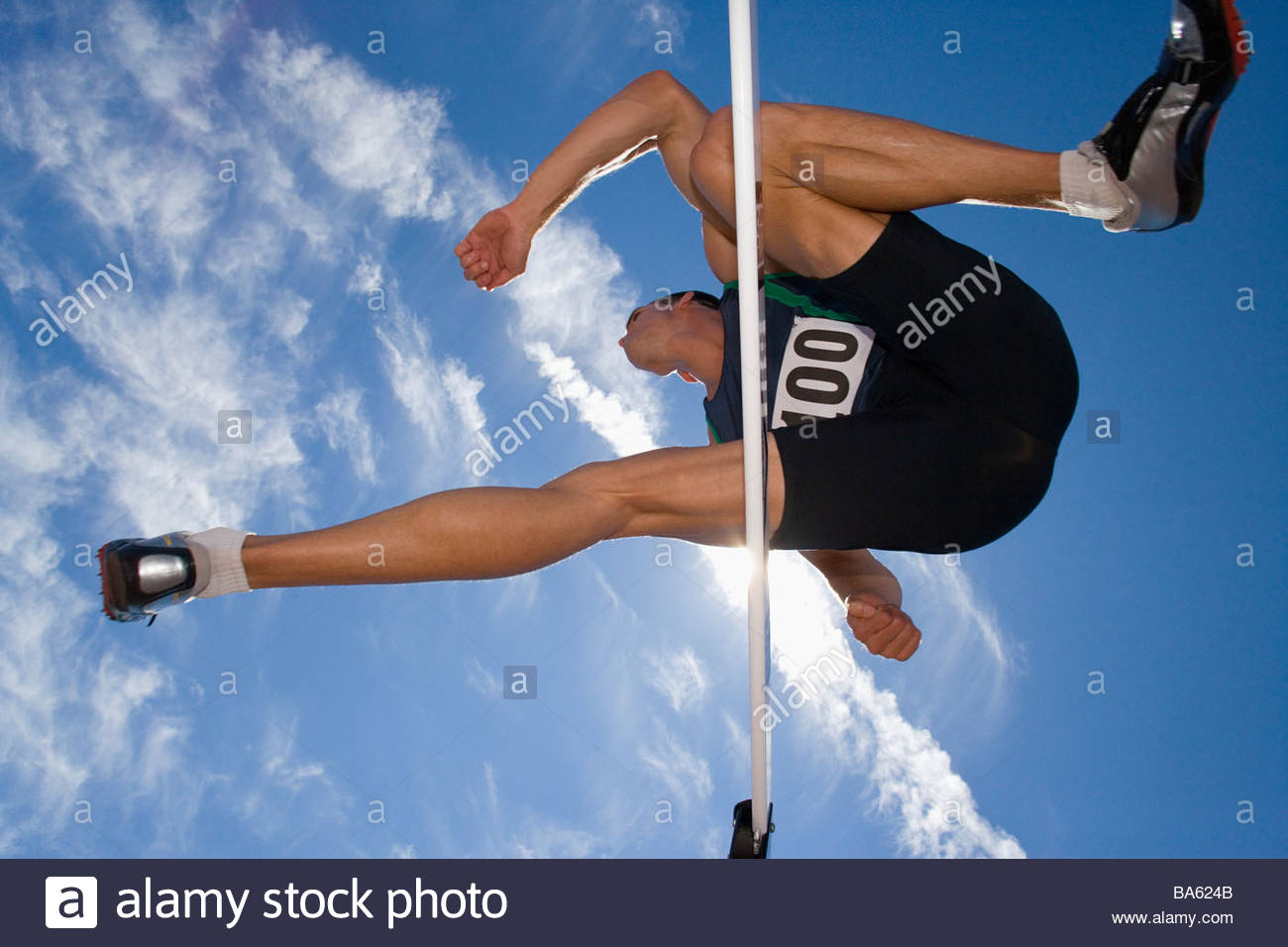Male athlete jumping over hurdle, view from below - Stock Image